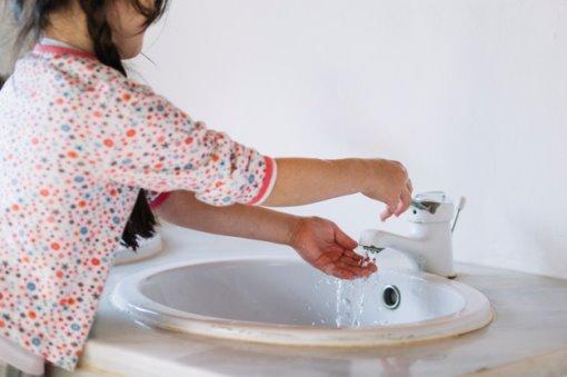 ילדה ליד ברז מים