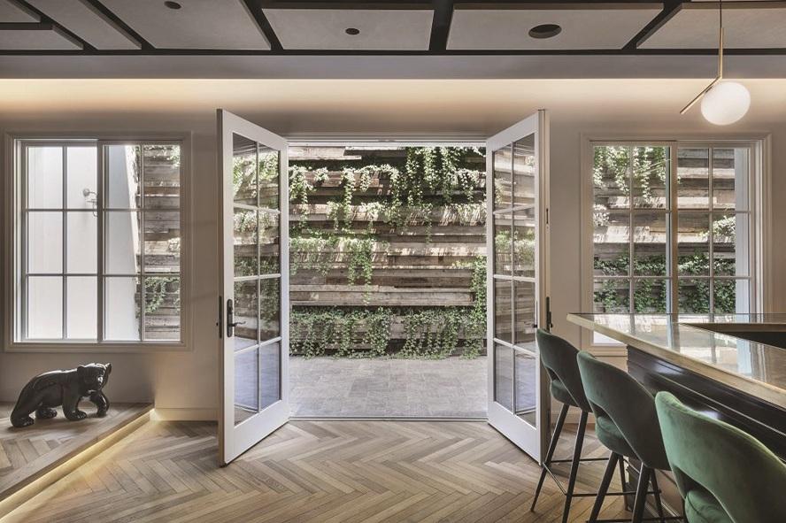 קיר עשוי קורות עץ ממוחזרות בשילוב צמחייה ירוקה. תכנון ועיצוב: שי דוד, חברת כרכום, עיצוב נוף. אדריכלות: שרון וייזר
