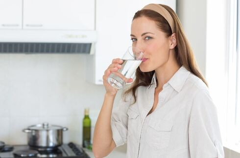 אישה שותה כוס מים